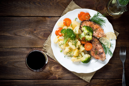 49265442 - grilled salmon steak garnished with vegetables. top view, style rustic.